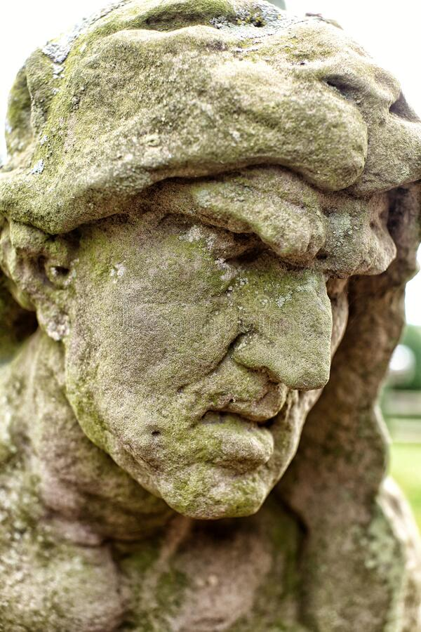 Statue of the man in lion hood with angry face. Stone statue of the man in lion hood with angry face royalty free stock photos