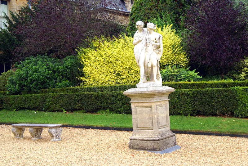 Statue of a man and a woman on a plinth and a seat in a garden. Statue of a couple and a seat in a garden for decoration. Cupid and Psyche statues stock image