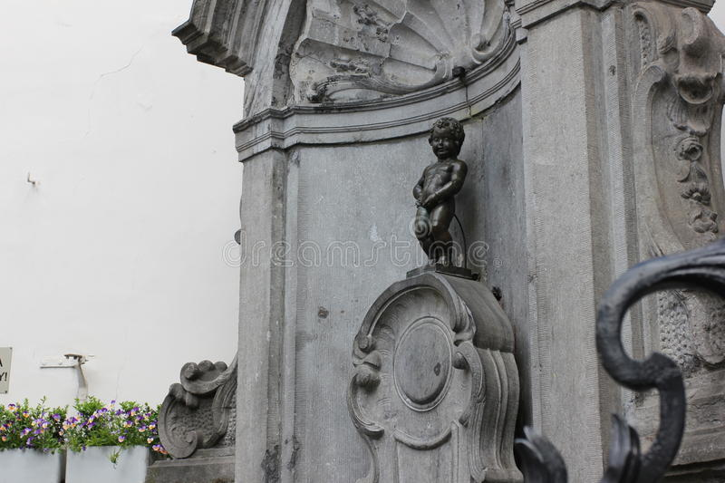 Statue of Manneken Pis in the center of Brussels, Belgium. Statue of fameous Manneken Pis outdoors in center of Brussels, Belgium, at the springtime daylight stock photo