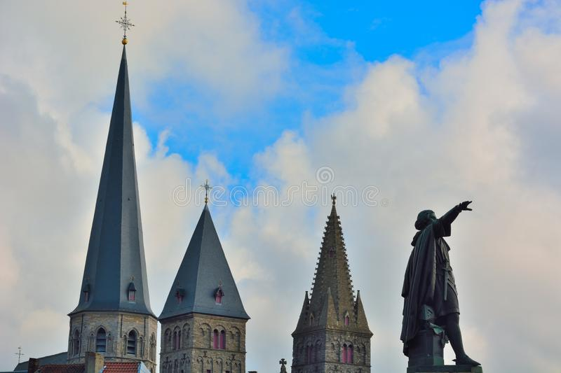 Statue of medieval man and chuch towers. In the clouded sky stock photos