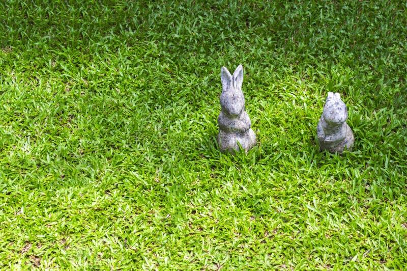 Statue mit zwei Kaninchen auf grünem Gras lizenzfreies stockfoto