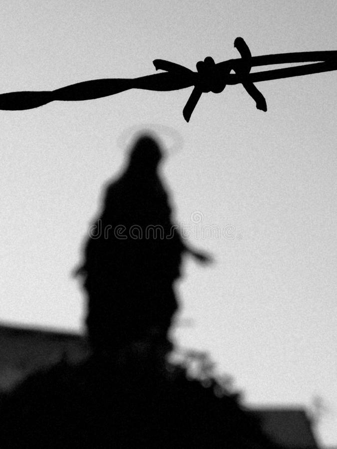 Statue of Mother Mary behind barbwire stock images