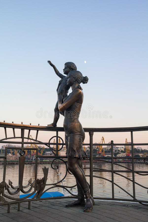Statue of mother and son greeting the sailor on the pier stock photos