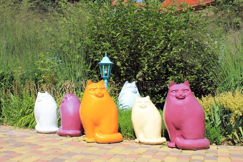 Statue multicolori del gatto in giardino fotografie stock libere da diritti