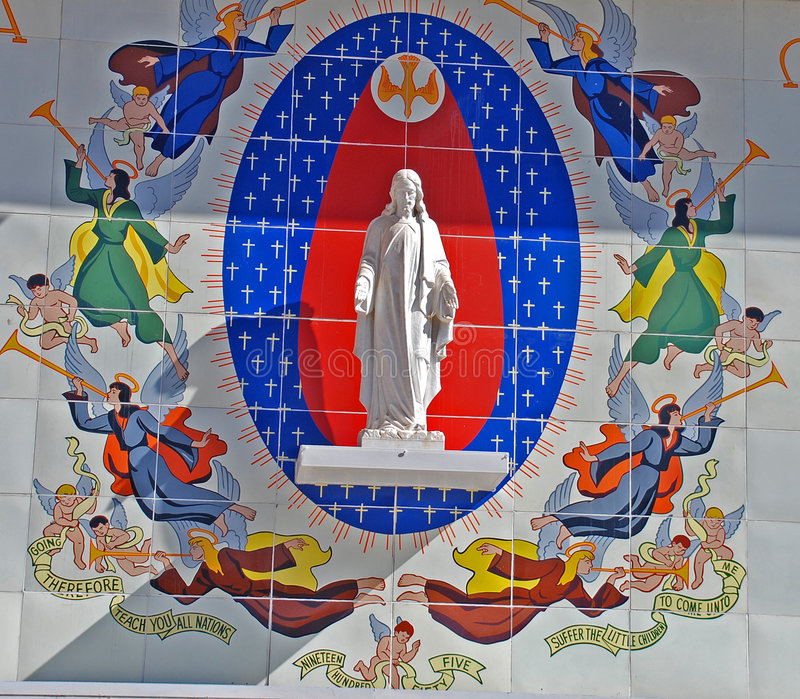 Statue and Mural of Jesus. This is a striking, colorful and creative expression of worship and spirituality. Angels and biblical themes are depicted in a mural stock photo
