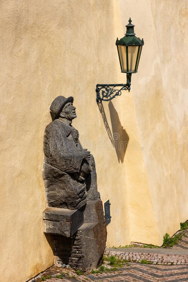 Statue of a musician on the stairs and a lantern with a shadow at Prague Castle royalty free stock photos