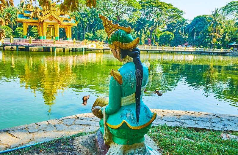 Nat statue in Theingottara park, Yangon, Myanmar. The statue of Nat spirit deity, sitting on the bank of a pond in Theingottara park, Yangon, Myanmar royalty free stock photo
