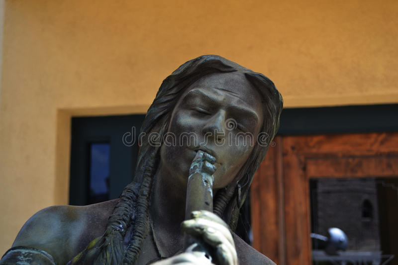 Statue of Native American Playing Flute. Statue of a Native American playing a flute taken on Main Street in Marble Falls, Texas stock photo