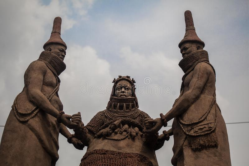 The Oba of Benin. A statue of the Oba of Benin sitting regally between two of his chiefs. The two men astride the king cautiously hold on to his arms, while he royalty free stock photos