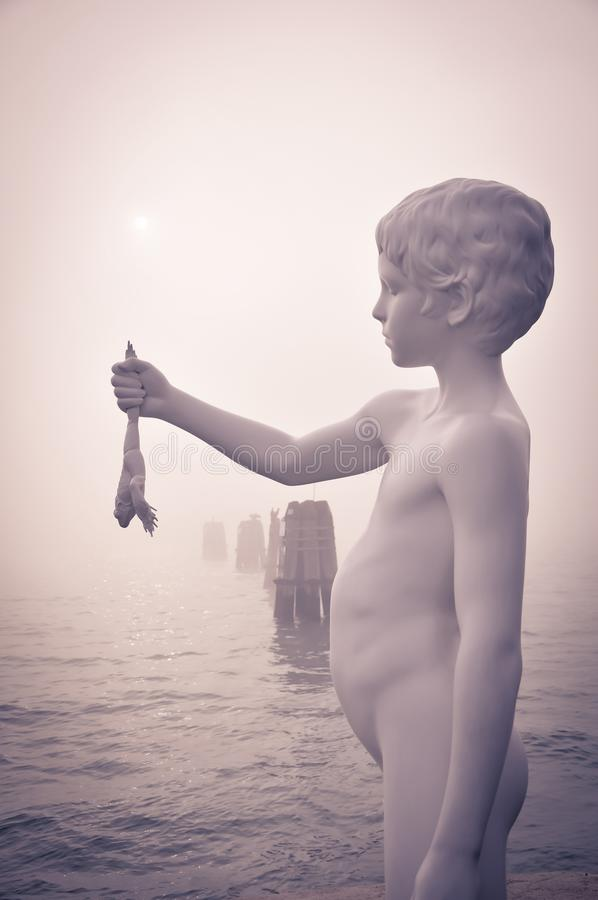 Free Statue Of The Boy With Frog On The Edges Of The Lagoon Of Venice Royalty Free Stock Photography - 103054297