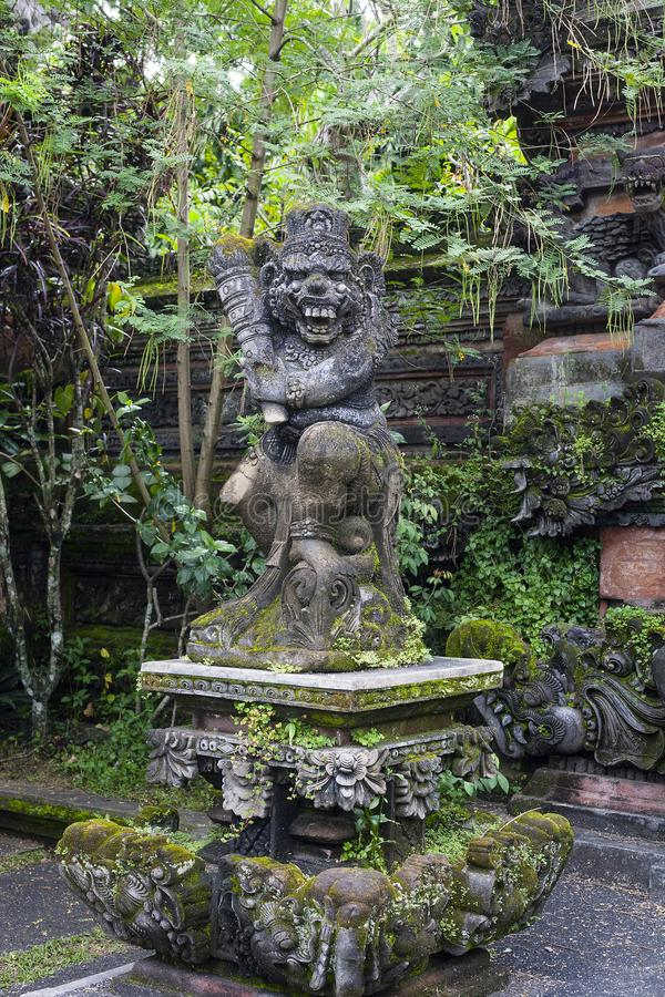 Statue of old stone cruel monkey Hindu temple, Ubud, Bali. Statue of old stone cruel monkey with weapon in traditional Hindu temple in Ubud, Bali, .Indonesia royalty free stock photography