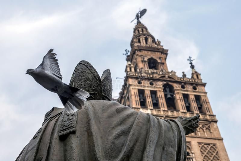 Statue opposite to the weather vane of Seville, pigeon initiates the flight, Andalusia, Spain. Conceptual image royalty free stock images