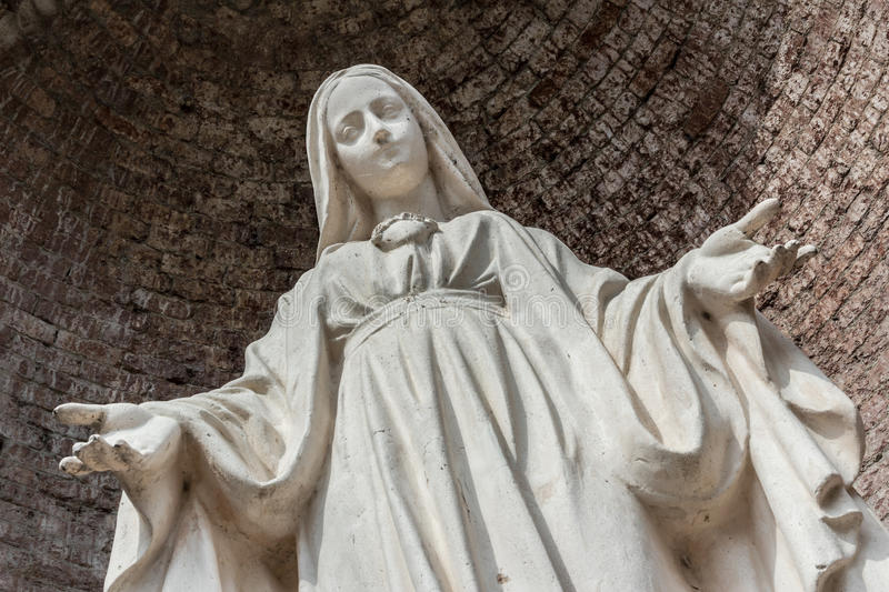 Statue of Our Lady. Close-up of Our Lady with open arms, bottom view stock photo