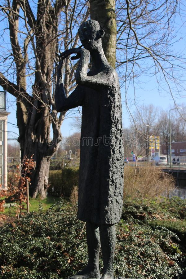 Statue of person who plays whistle by Jan Snoeck created in 1960 and on the street in voorburg, the Netherlands. Statue of person who plays whistle by Jan royalty free stock photos
