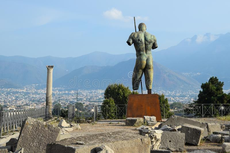 Statue at Pompeii with some ruins royalty free stock images