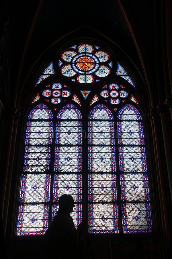 Stained Glass Window with Silhouette Interior Notre Dame Cathedral. A statue in prayer is silhouetted against the vibrant stained glass windows of Notre Dame royalty free stock images