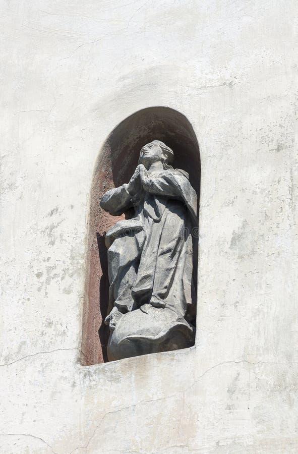 Statue of praying man in a wall niche. Lviv. Statue of a praying man in a outdoor wall niche in Lviv street, Ukraine stock photography