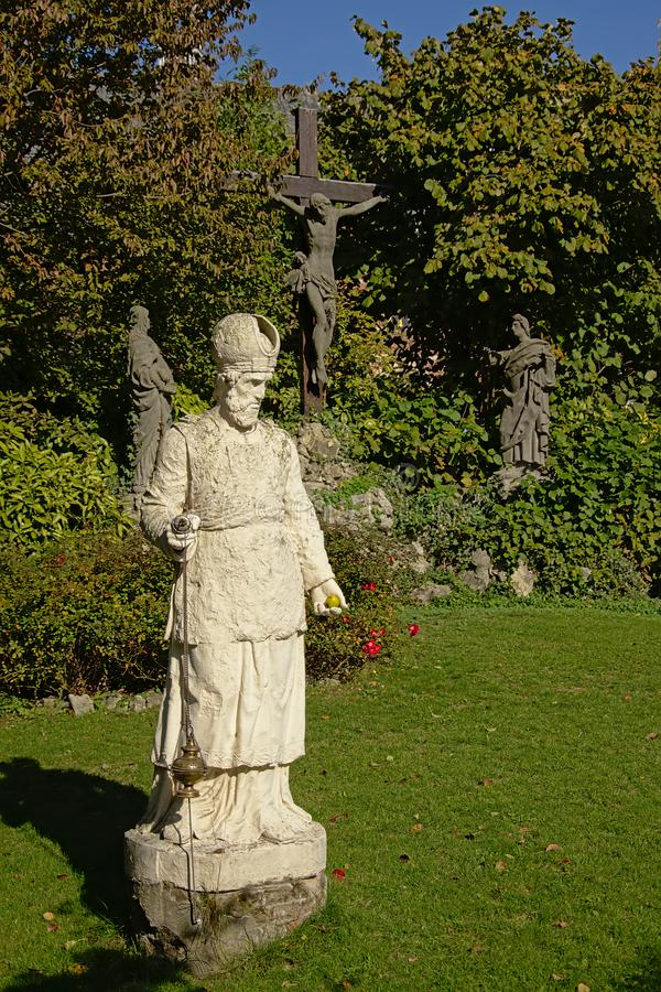 Statue of a priest in front of Jesus on the cross with Mary and Mary Magadelen kneeling next to it stock photo