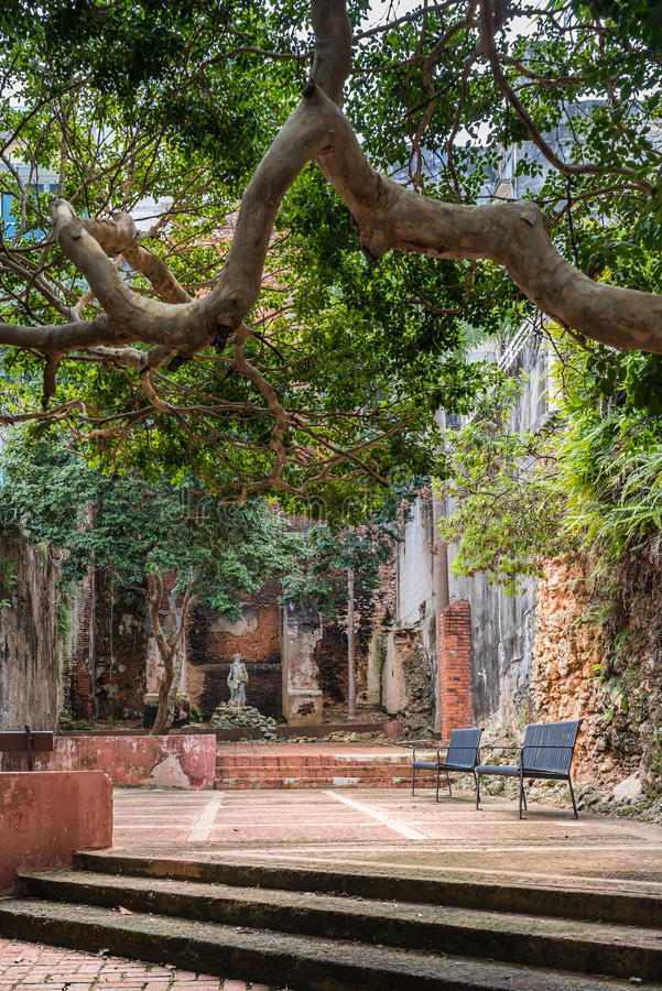 Statue in public courtyard with benches. Brick walls in disrepa. Ir. Grungy and in ruins. Covered by large shade trees royalty free stock photo