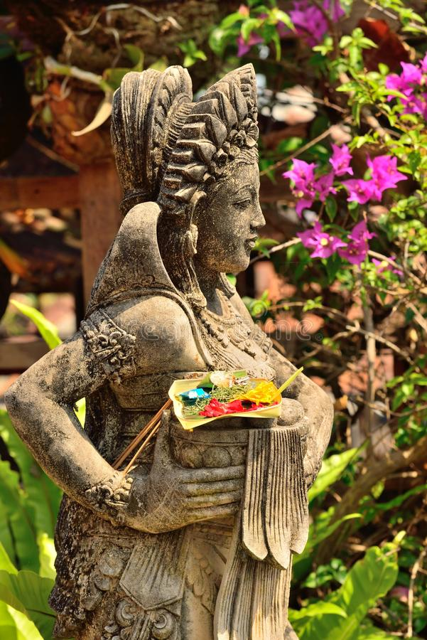 Statue in Pura Tanah Lot with offering, Bali stock photo
