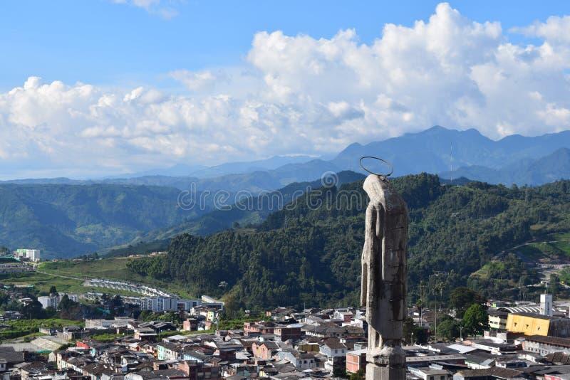 Statue regardant au-dessus de la ville et des montagnes photo libre de droits