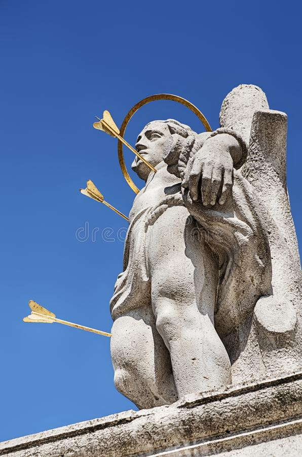 Saint With Arrows. A statue of a saint on Castle Hill is punctured by three golden arrows in Budapest, Hungary royalty free stock photos