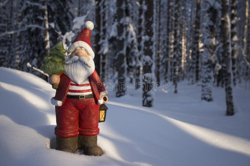 Statue of Santa Claus with a Christmas tree and lamp. Background. Statue of tiny Santa Claus in the winter forest with a Christmas tree and lamp take a royalty free stock photo