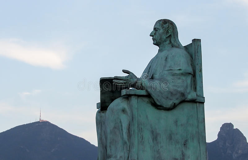Statue of a Seated Man over Mountains stock photo