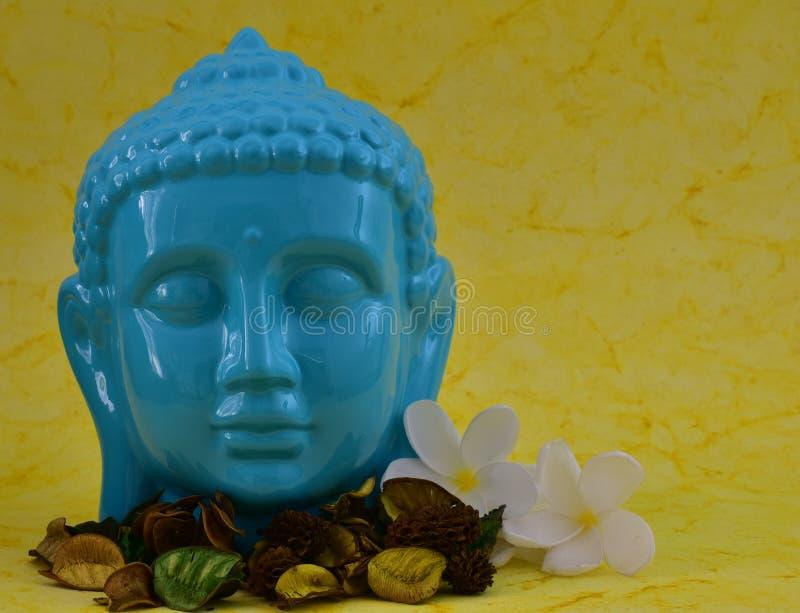 Statue sereine de visage de couleur bleue en céramique de Bouddha avec des fleurs sur le fond jaune coloré photographie stock