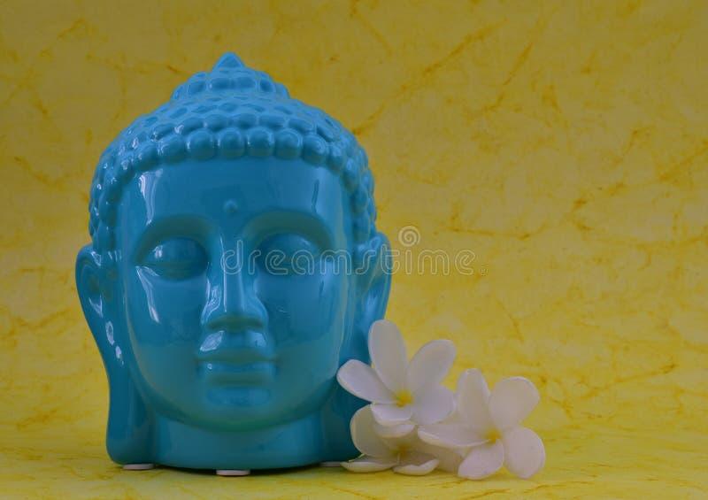 Statue sereine de visage de couleur bleue en céramique de Bouddha avec des fleurs sur le fond jaune coloré photos libres de droits
