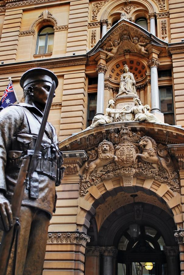 A statue of a soldier with the australian flag, the General Post Office Building in the background. stock photos