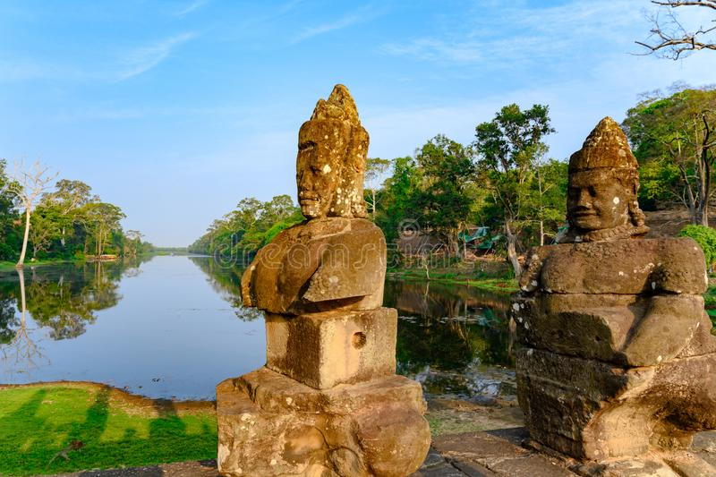 Statues on South Bridge, Entrance of Angkor Thom, Khmer styled Temple, Siem Reap, Cambodia. Two of the smiling face sin Angkor Thom. Angkor Thom built in the stock images