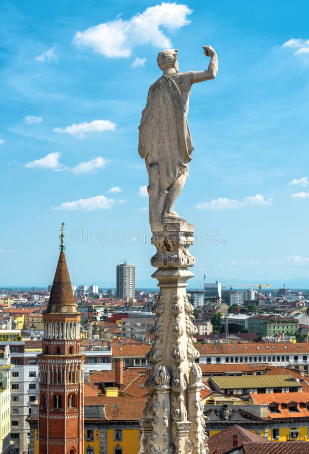 Statue on spire of Milan Cathedral on blue sky background, Milan, Italy. Detail of roof overlooking Milano city in summer stock photo