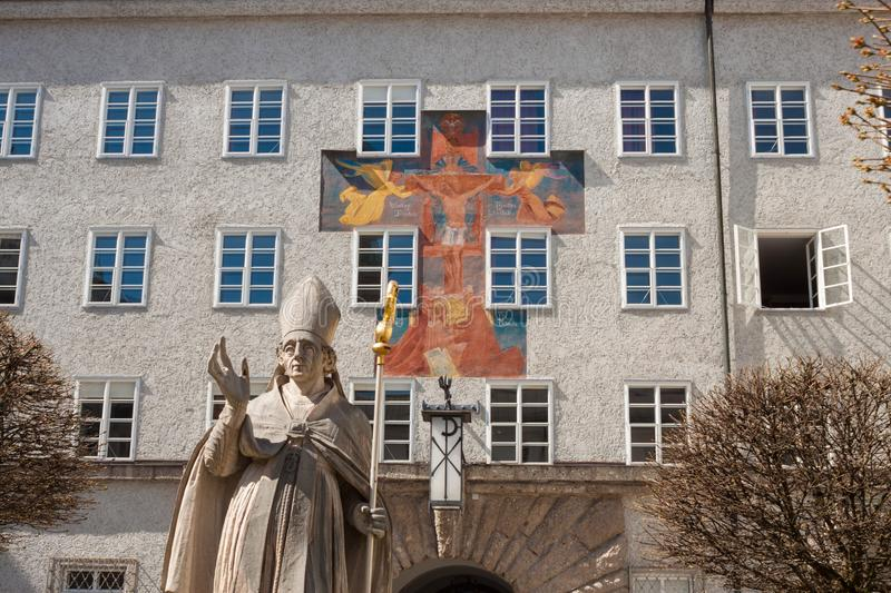 Statue of St. Rupert and fresco on the wall of St.Benedict college, Salzburg, Austria stock image