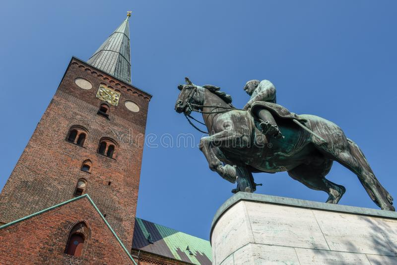 Statue and 13th century Cathedral at Aarhus in Denmark stock images