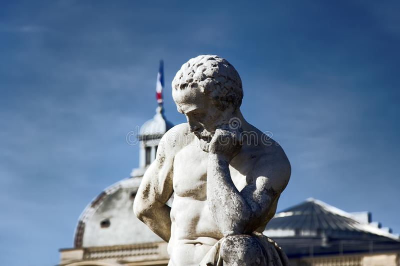 The statue of the Thinker. Paris, France - 22.09.2017: The statue of the Thinker against the Church dome stock photography