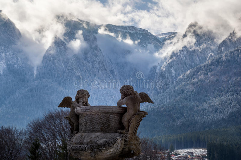 Statue of two angels looking each other, with a mountain in background royalty free stock photo