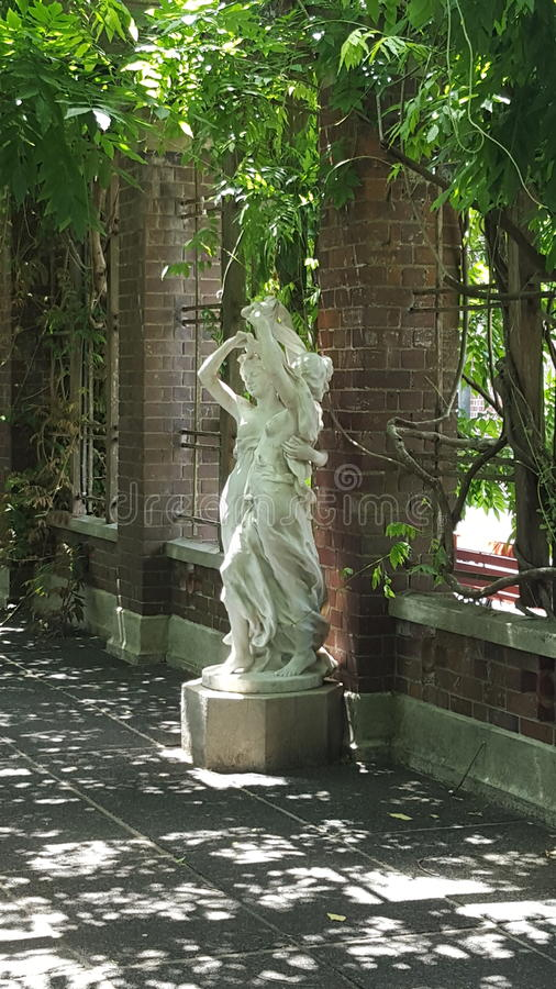 Statue of two ladies in a garden - shade with sunshine shining through royalty free stock photography