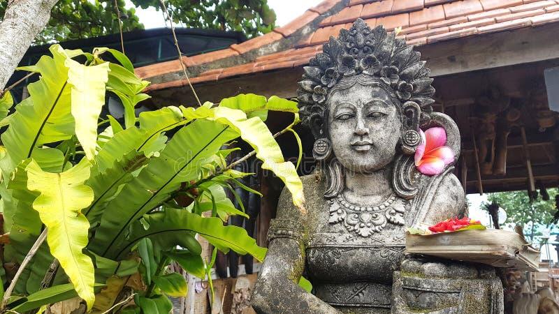 Statue und Balinese, die in Bali anbieten stockfotografie
