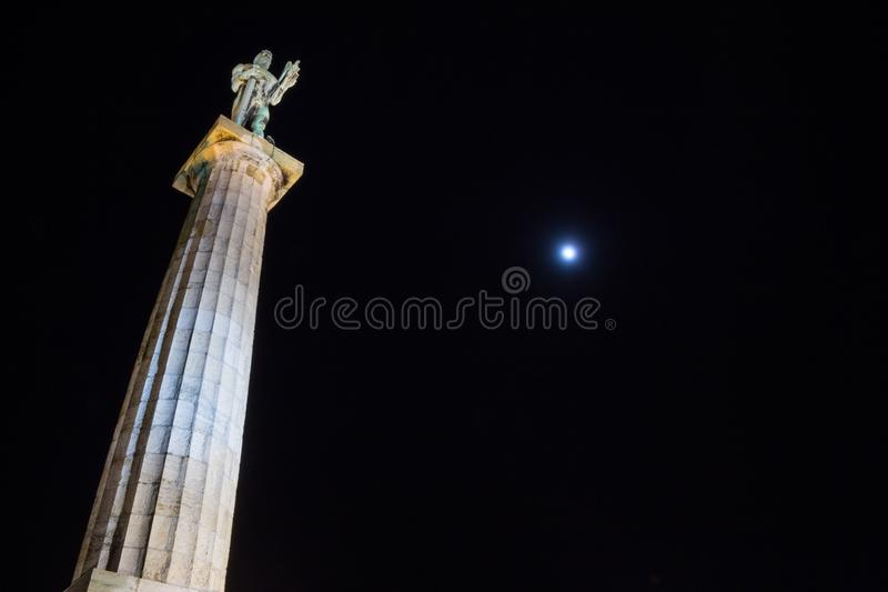 Statue of the Victor Pobednik, or Viktor in Serbian on Kalemegdan fortress in belgrade, Serbia. Taken at night, the moon being visible in the background royalty free stock photos