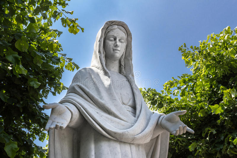 Statue of Virgina Mary. Statue of the Blessed Virgin Mary among trees stock images