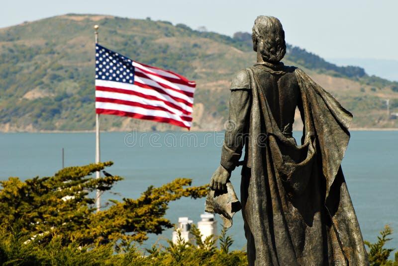 Statue von Christopher Columbus und VON USA-Markierungsfahne stockbilder