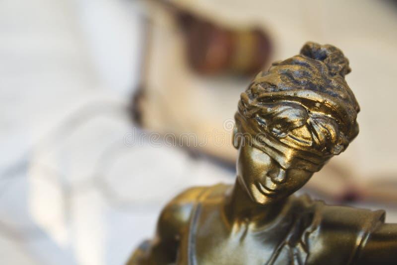 Statue von Gerechtigkeit, von Richterhammer und von offenen Büchern stockfoto