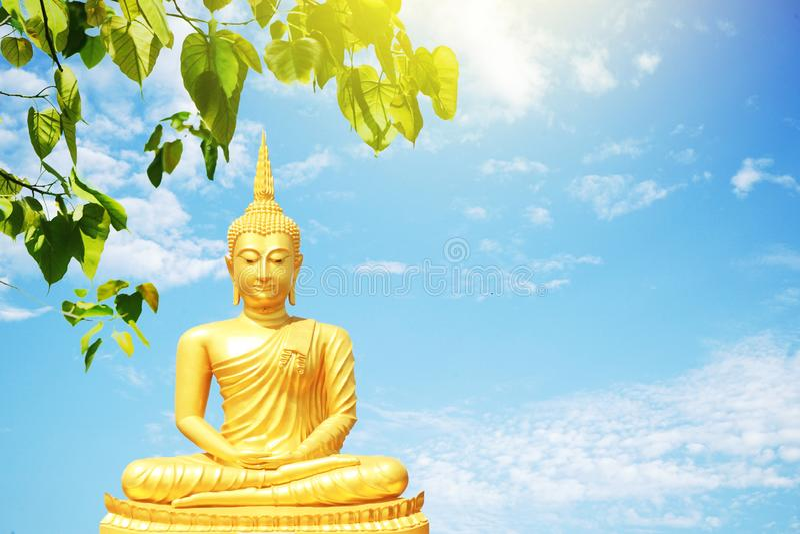 Statue von goldenem Buddha sitzend auf einem Bretterboden unter dem Hintergrund BO-Blattes und des blauen Himmels stockbild