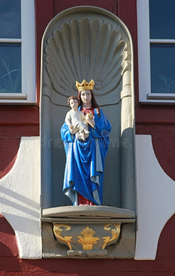 Statue von Jungfrau Maria mit Kind Jesus an einem alten Fachwerk- h stockfotos