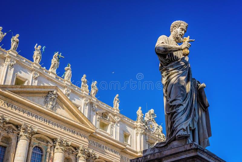 Statue von St Peter in St Peter Quadrat, Vatikanstadt, mit der Front der berühmten Basilika lizenzfreies stockfoto