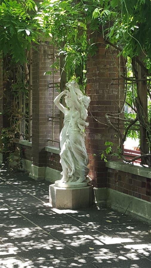 Statue von zwei Damen in einem Garten - Schatten mit dem Sonnenschein, der durch glänzt lizenzfreie stockfotografie