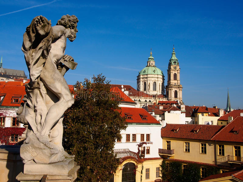 Statue in Vrtbovska Garden on the background Saint Nicholas Church, Prague, Czech Republic. Middle terrace: the sculptural decoration of the garden, Sunny day stock image