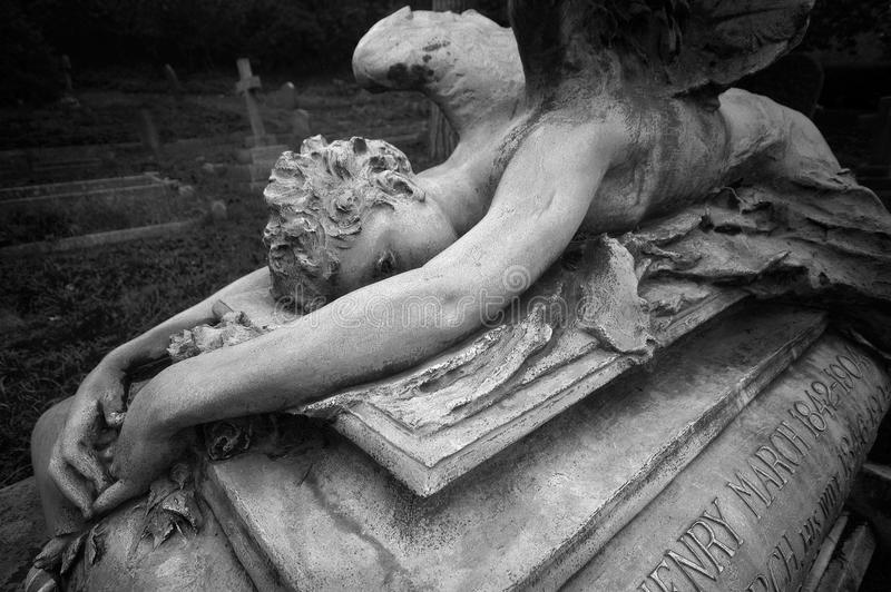 Statue of a weeping angel laying over an ancient grave stock photography