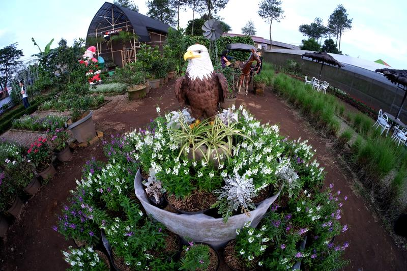 Statue white eagle head with brown fur in the flowers garden side by side with horse statue and santa claus statue stock image